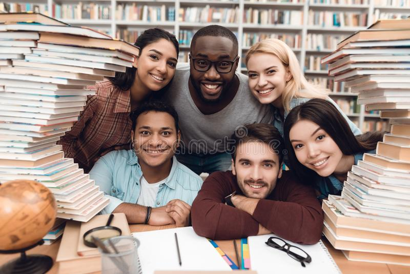 Six ethnic students, mixed race, indian, asian, african american and white surrounded with books at library. stock photo