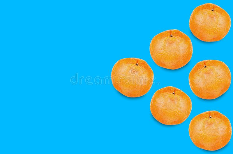 Six fresh whole delicious orange mandarins in form of triangle on blue background with copy space for your text. Concept of food or celebration stock image