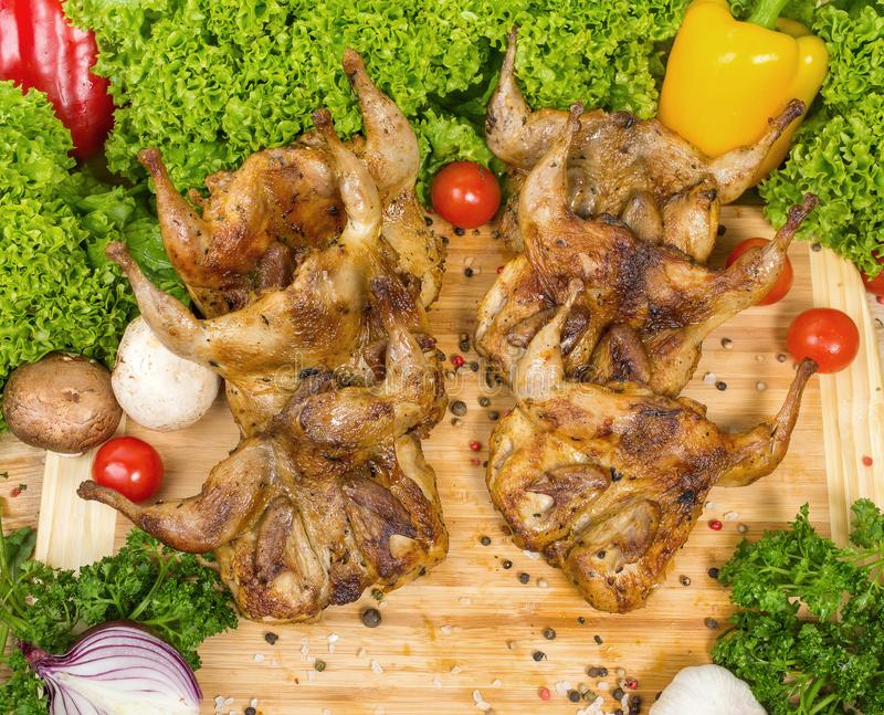 Six fried chicken lie entirely on a wooden board with cherry tomatoes, lettuce leaves, garlic, chili, rosemary, onion royalty free stock images