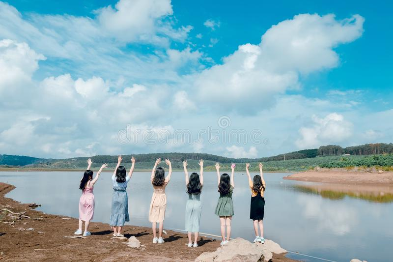 Six Girls Raise Their Hands in Front of Body of Water stock image