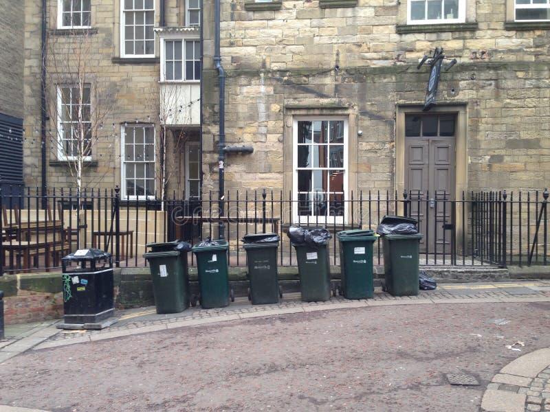 Six green rubbish bins in a line stock image
