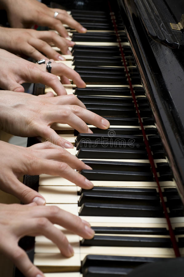 Six hands on piano. Six hands palying old piano stock images