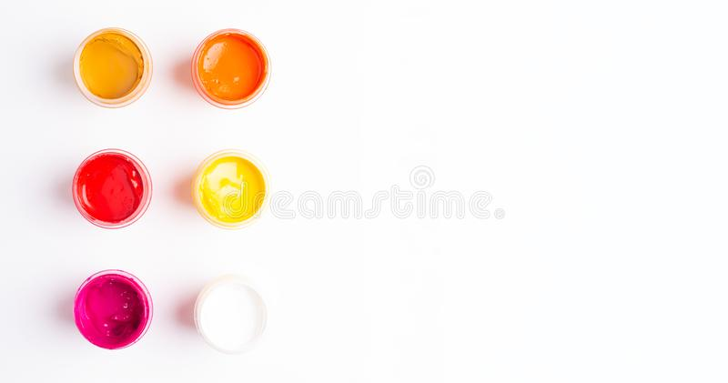 Six jars of paint on a white background Isolated Multicolored gouache Top view. Copy space royalty free stock image