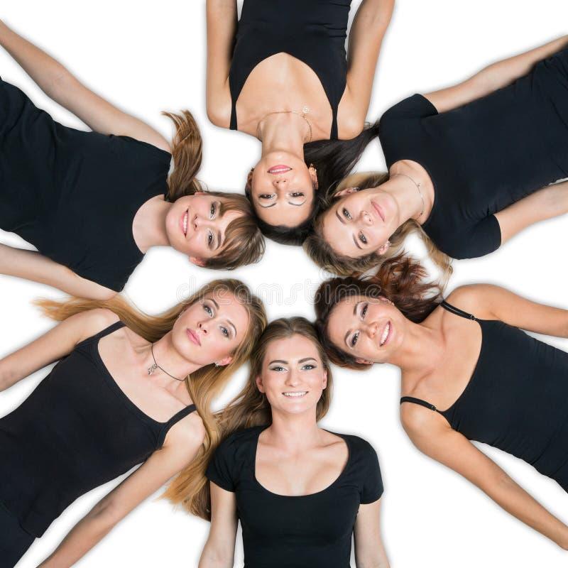 Six jeunes femmes s'étendant en cercle photos libres de droits