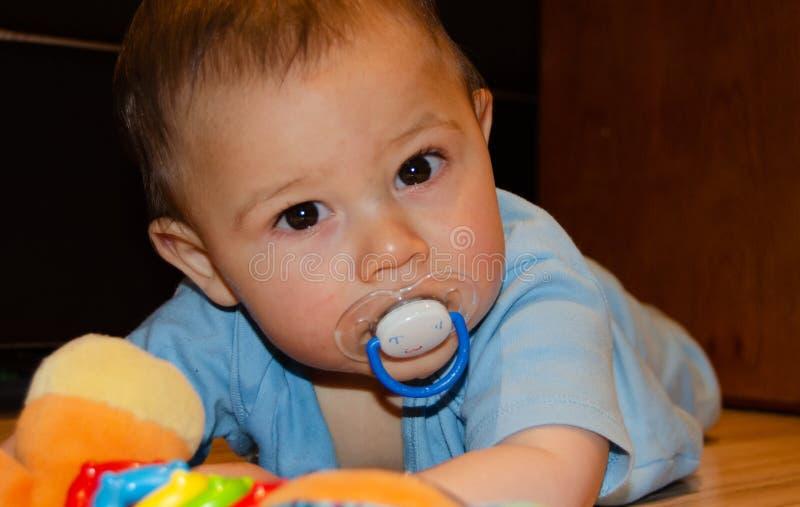 Six mois mignons de b?b? gar?on jouant sur Flor avec le jouet de dentition, d?veloppement pr?coce et faisant ses dents le concept photo libre de droits