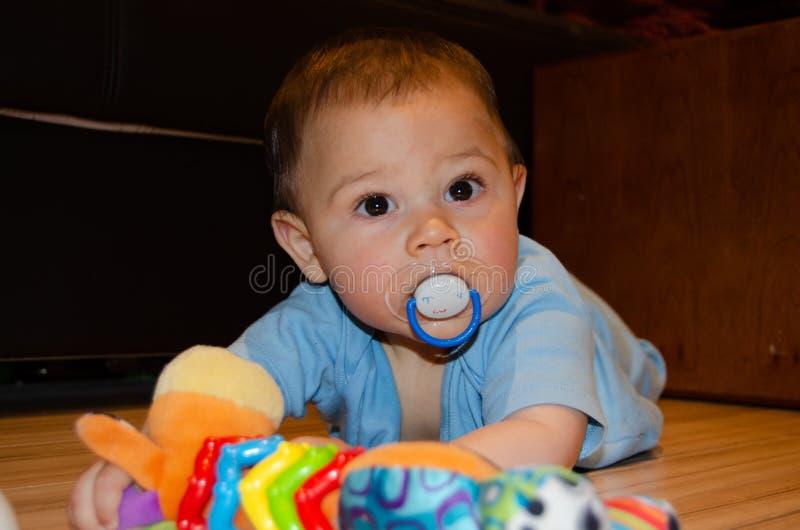 Six mois mignons de b?b? gar?on jouant sur Flor avec le jouet de dentition, d?veloppement pr?coce et faisant ses dents le concept photographie stock libre de droits