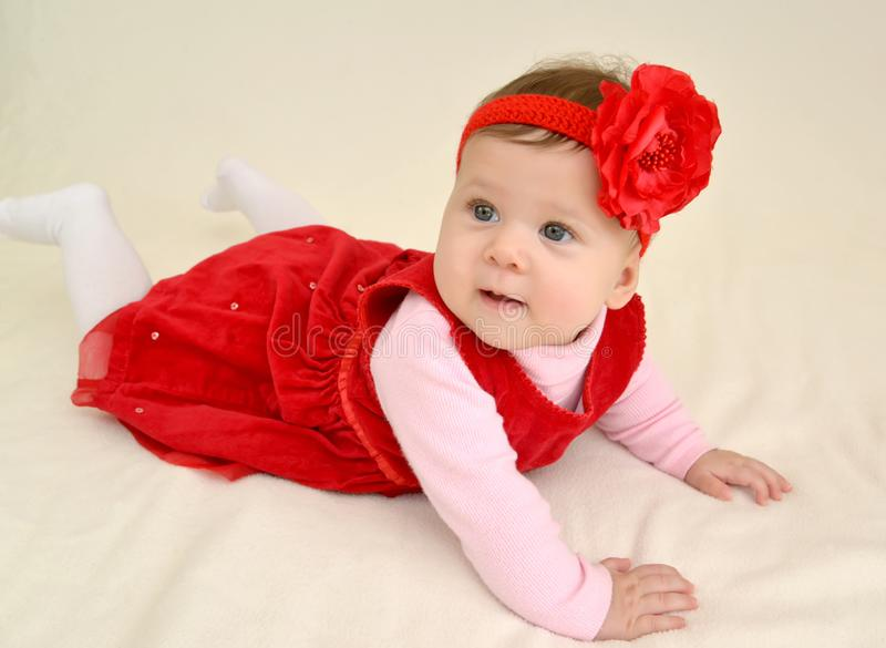 The six-months girl with a red flower on the head lies on a stomach royalty free stock image