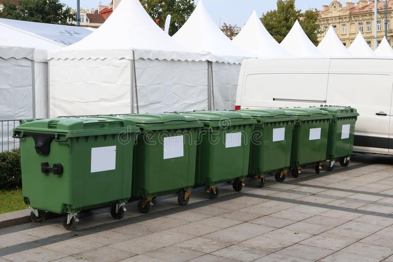 Six new plastic green garbage containers. Back side of the city stock image