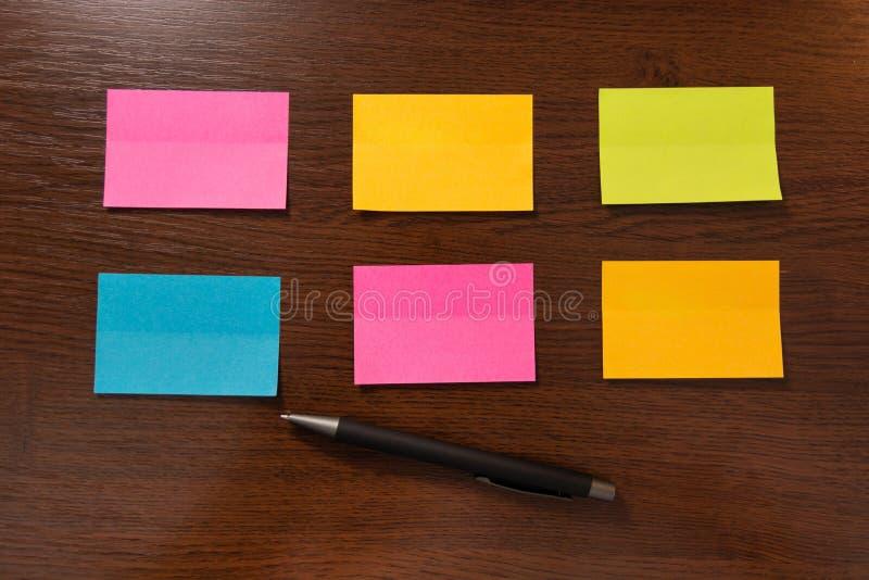 Six notes collantes colorées dans la rangée deux et stylo sur le bureau en bois brun photos stock