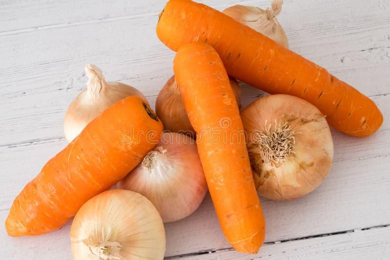 Six oignons cultivés écossais d'or et trois carottes un de vos cinq un jour dans la consommation saine image libre de droits