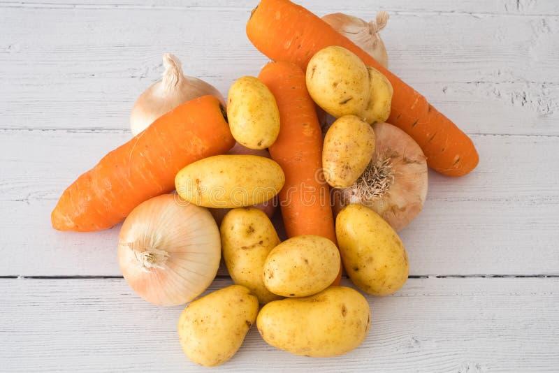 Six oignons cultivés écossais d'or, quelques pommes de terre et trois carottes un de vos cinq un jour dans la consommation saine image stock