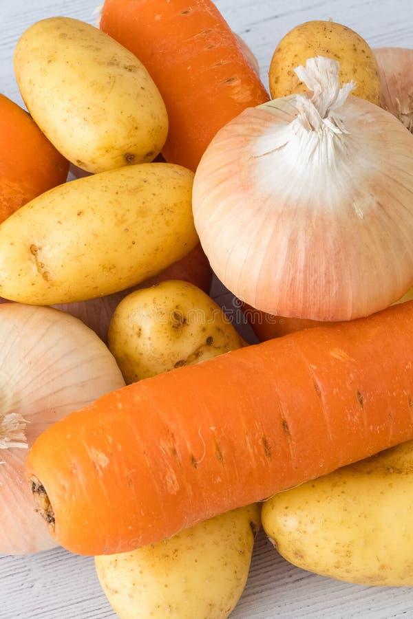 Six oignons cultivés écossais d'or, quelques pommes de terre et trois carottes un de vos cinq un jour dans la consommation saine photo stock
