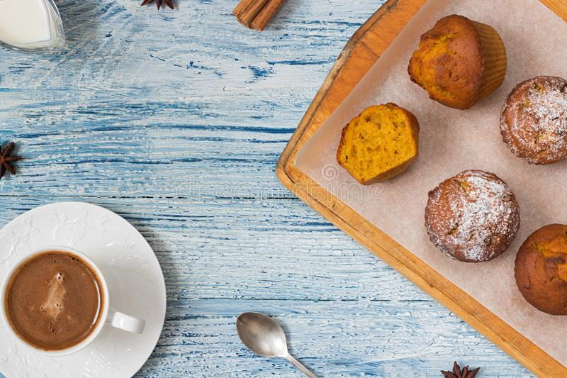 Pumpkin muffins on light blue background with ingredients stock photo