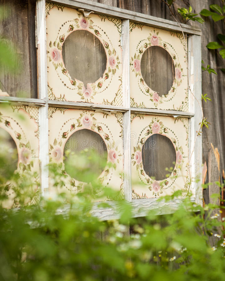 Six paneled old window painted hanging on a wooden fence with green bushes surrounding. Cream with pink flowers painted on a six panel window pain hanging on a stock photo