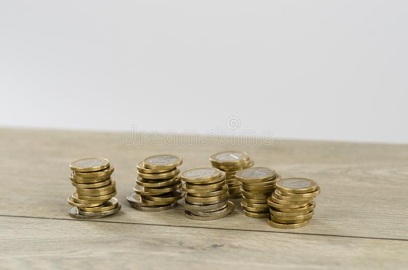 Pile of 1 Euro coins. Six piles of 1 euro coins on wooden floor in studio royalty free stock photography