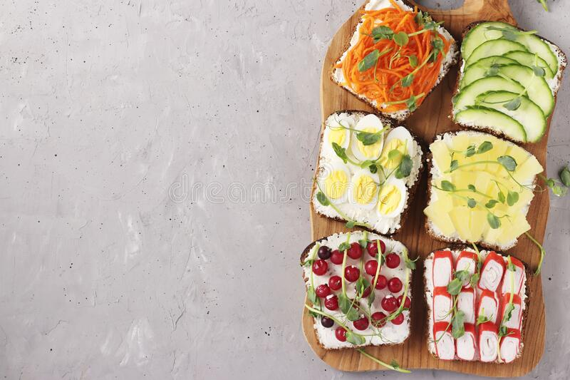 Six sandwiches on toast with fresh carrots, cucumbers, pineapple, red currant, crab sticks and quail eggs with peas microgreens on. Wooden board on gray royalty free stock image