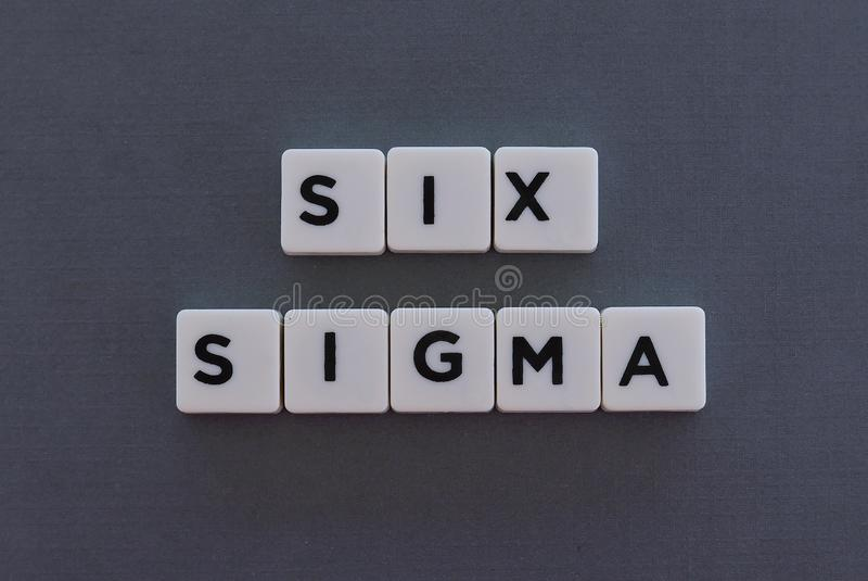 Six Sigma word made of square letter word on grey background. Manufacturing continuous process business management measure improvement lean development industry royalty free stock photos