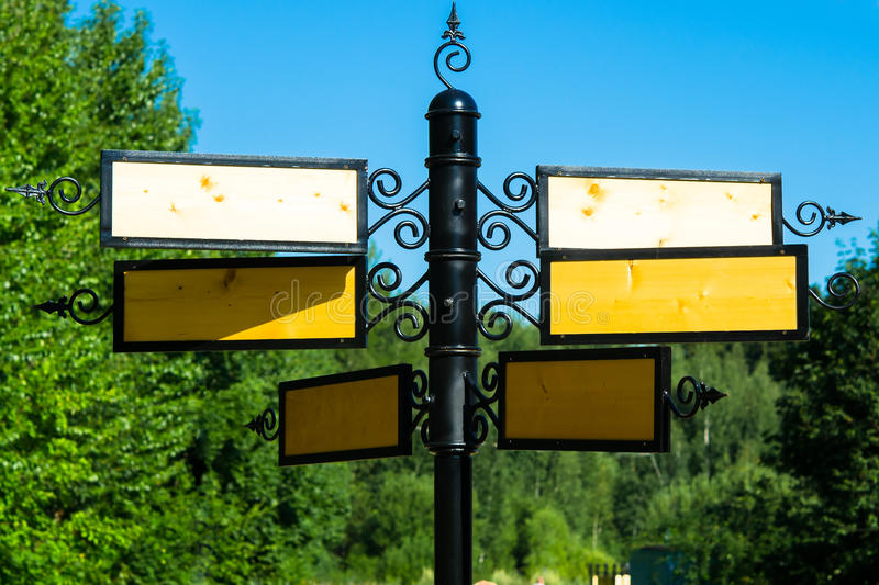 Six signs on a pole in the sky. Signs blank for your inscription stock photography