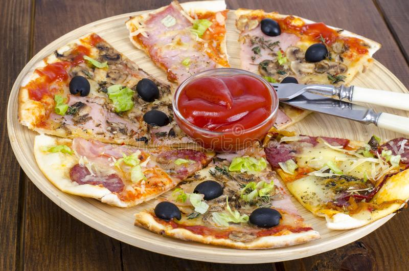 Six slices of pizza with different toppings on wooden board royalty free stock image