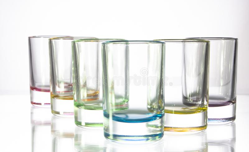 Six small colorful glasses on a white background royalty free stock images