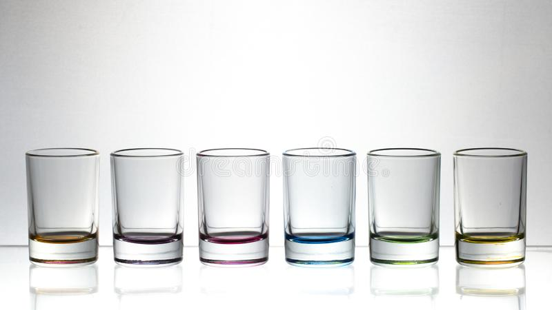 Six small multi-colored glasses on a bright background stock image
