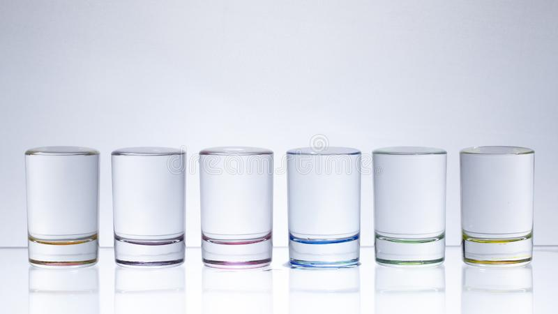 Six small multi-colored glasses on a bright background royalty free stock photography