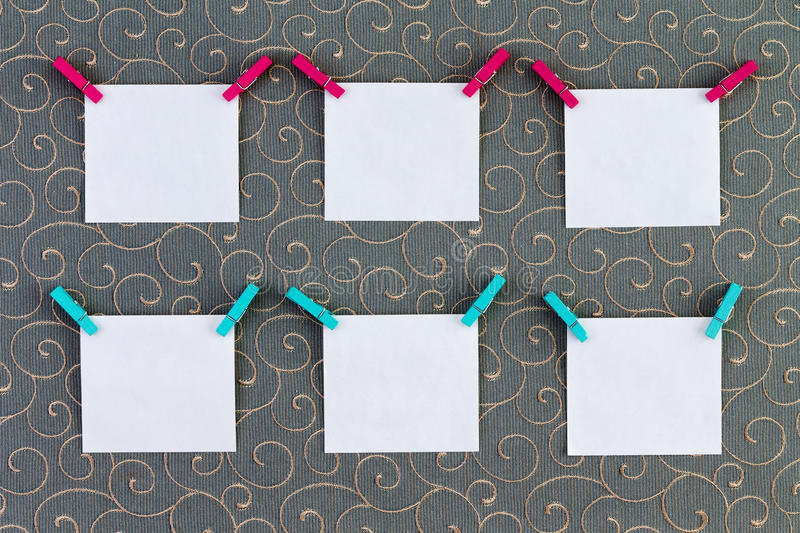 Six square tags with clothespins attached. Six square item or note paper tags with clothespins attached on top corners over cotton thread gray background stock images