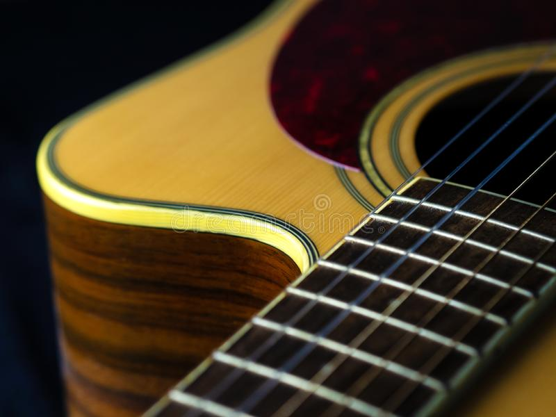 Six - string acoustic guitar  on a black background. low key. Music day stock image