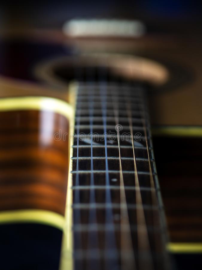 Six - string acoustic guitar  on a black background. low key. Music day royalty free stock photos