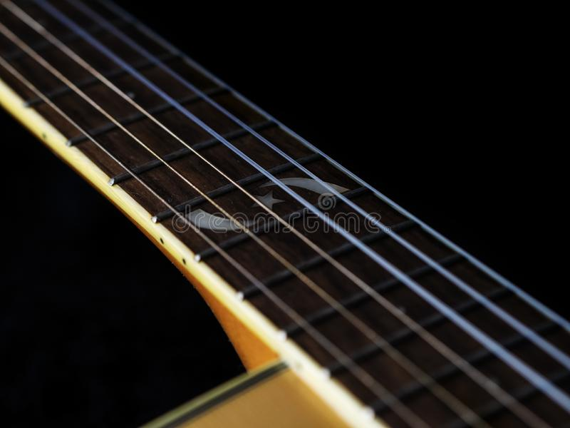 Six - string acoustic guitar  on a black background. low key. Music day royalty free stock photo