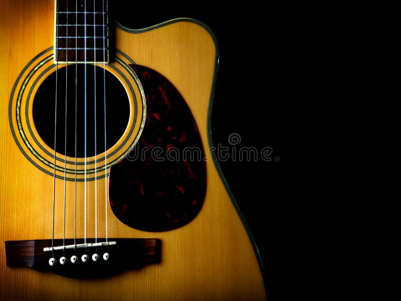 Six - string acoustic guitar on a black background. low key. Six - string acoustic guitar  on a black background. low key. music day stock photos