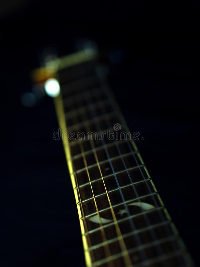 Six - string acoustic guitar  on a black background. low key. Music day royalty free stock image
