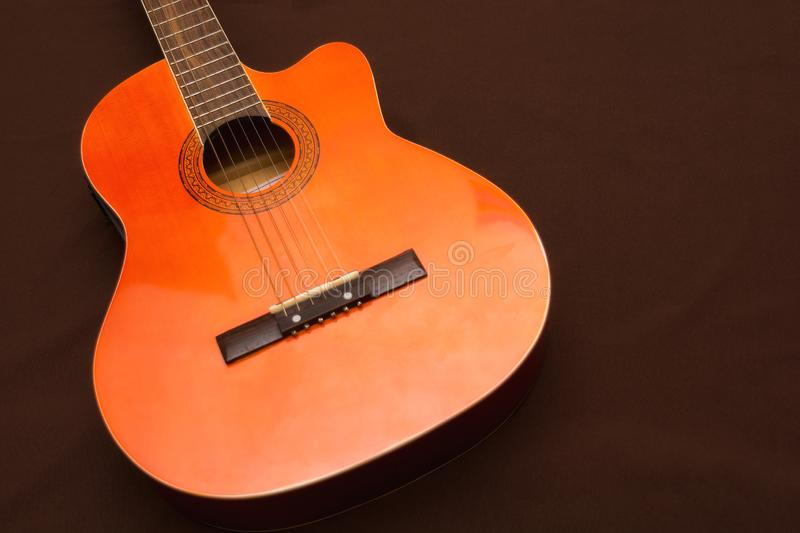 Six-string acoustic guitar on a dark brown background. Classical Spanish guitar. Musical instrument. Place for text royalty free stock photography