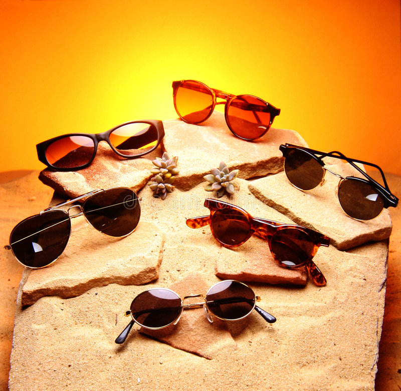 Six sunglasses over sand and stones royalty free stock photography
