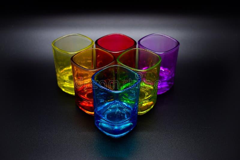 Six verres à liqueur multicolores placés dans la triangle sur le fond noir photo libre de droits