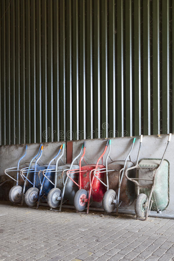 Free Six Wheelbarrows Rest Against Wall Of Farm Barn Stock Images - 54810464