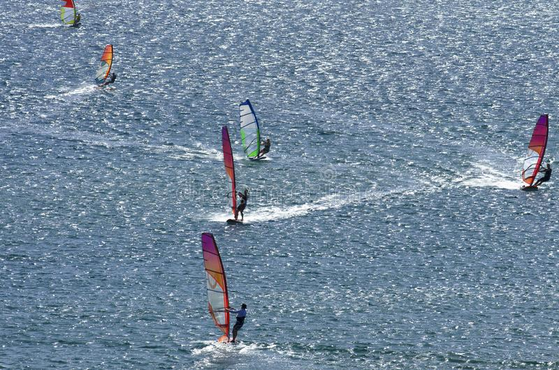 Six windsurfers are riding on the surface of the Mediterranean sea. Six windsurfers are riding on the surface of the dazzling beautiful Mediterranean sea stock photo