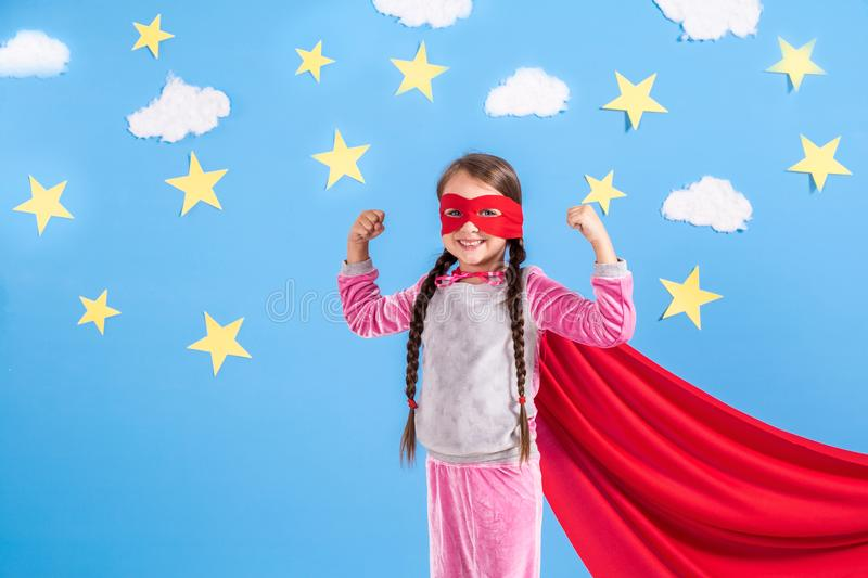 Six year blonde girl dressed like superhero having fun at home. Kid on the background of bright blue wall. Six year blonde girl dressed like superhero having stock image