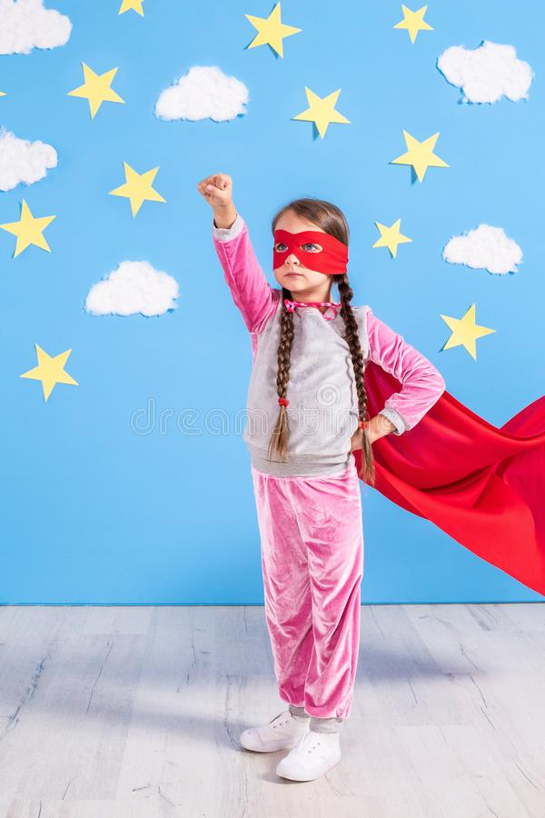 Six year blonde girl dressed like superhero having fun at home. Kid on the background of bright blue wall. stock photos