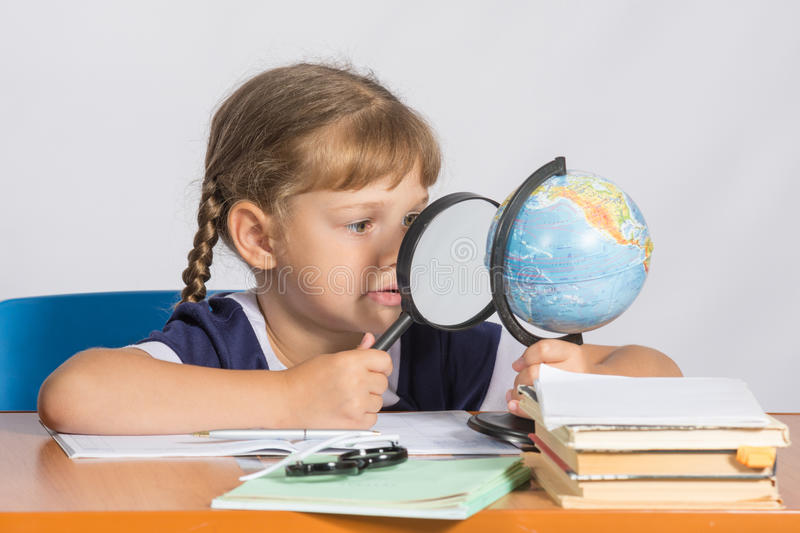 Six-year girl sitting at table and looks at the globe through a magnifying glass stock photo