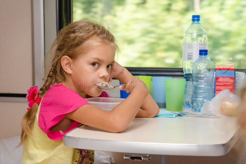 A six-year girl in a train sitting at table on the lower place in the second-class compartment of the car and eats porridge sp stock image