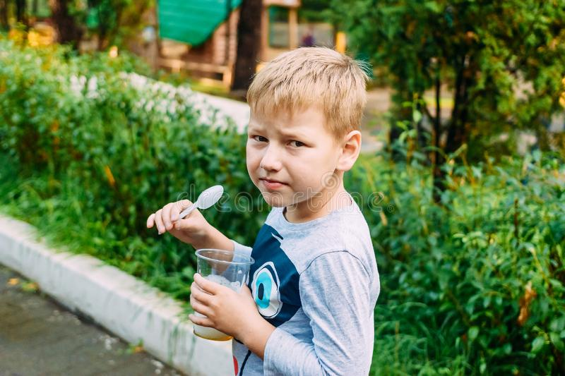 Six-year-old boy eats a plastic spoon useful oxygen cocktail stock photography