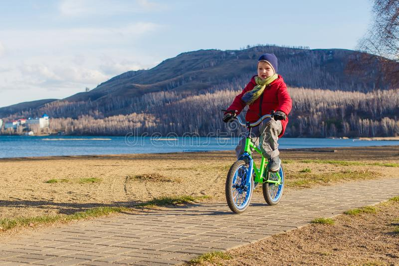 Six-year-old boy in a jacket, scarf and hat rides a two-wheeled children`s bike on the sidewalk on the background of the mountain. S and the sea in spring royalty free stock photography
