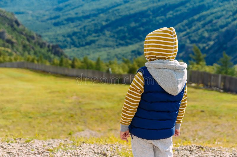 A six-year-old boy in warm clothes stands with his back against the background of a beautiful mountain landscape stock image