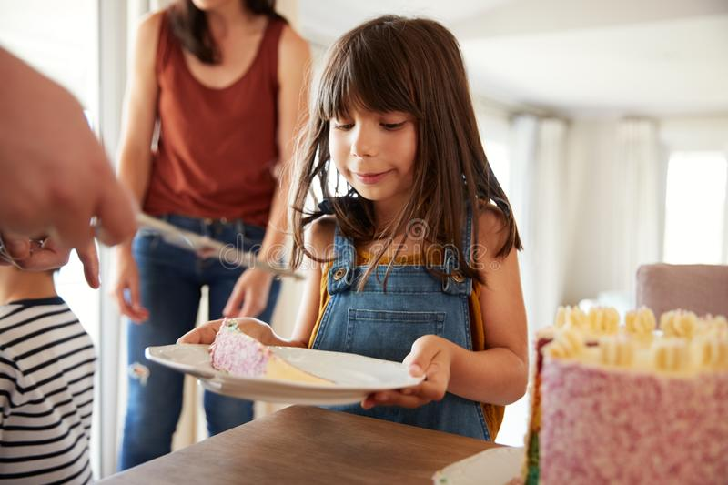 Six year old girl being served  birthday cake during a family celebration, close up stock images