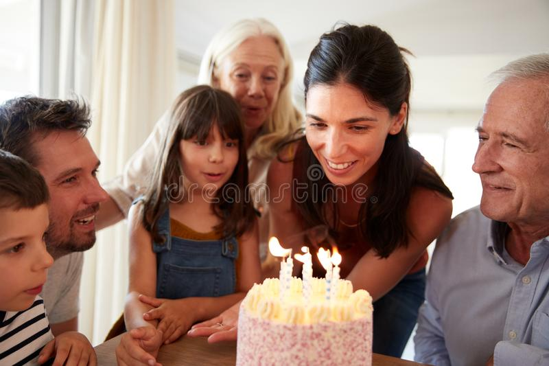 Six year old girl blowing out the candles on birthday cake watched by her mum and family, close up stock images