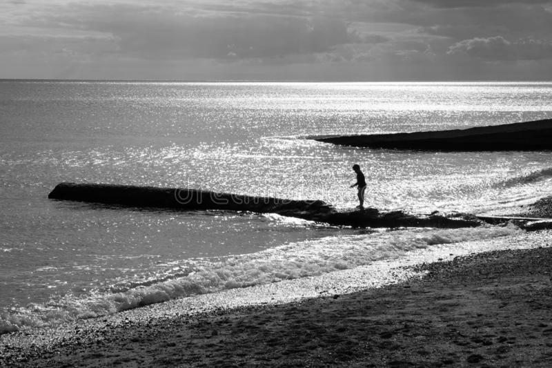 A six year old unrecognisable boy walking along a jetty in the sea, black and white photograph. A six year old unrecognisable boy in the distance walking along a stock photos