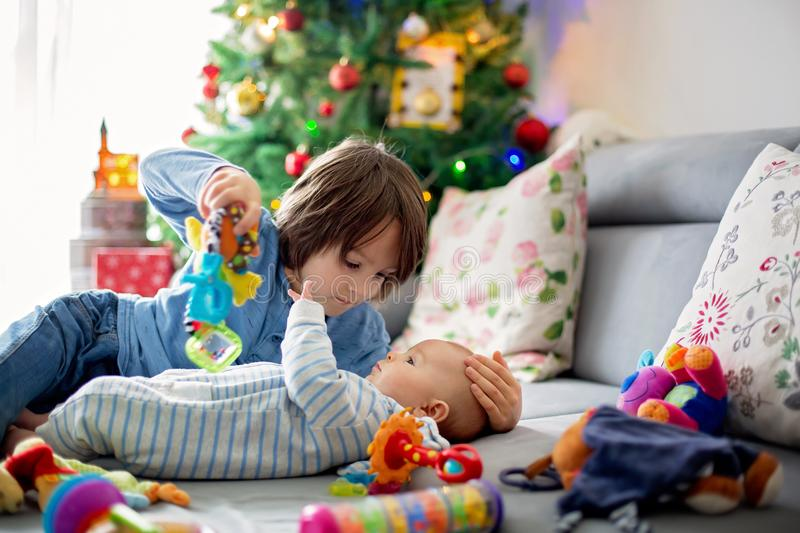 Six years old preschool boy, playing at home with his newborn ba. By brother, baby home activity. tenderness and care between siblings, family concept stock photos