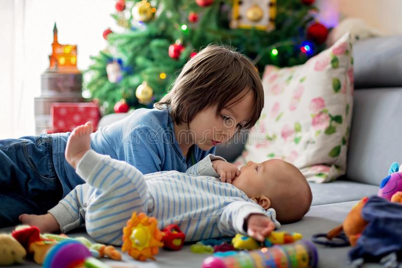Six years old preschool boy, playing at home with his newborn ba. By brother, baby home activity. tenderness and care between siblings, family concept stock photo