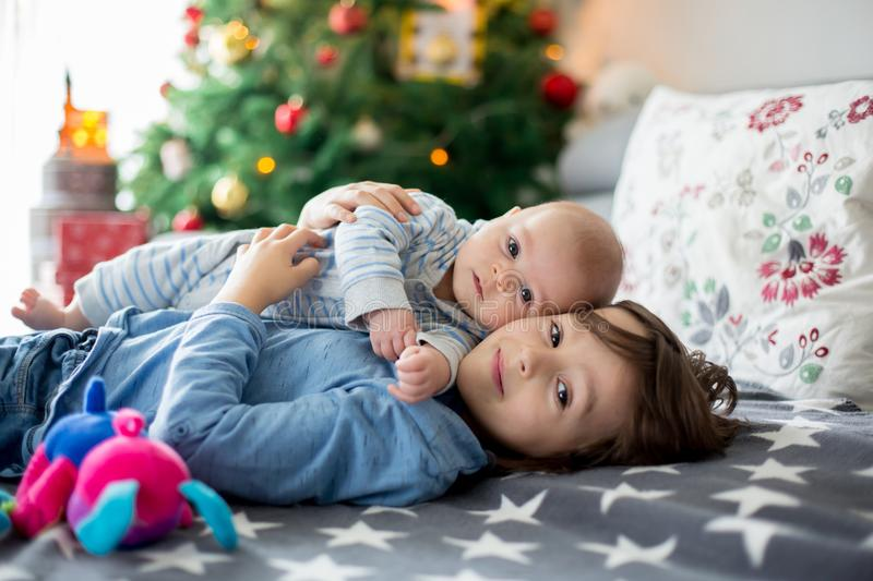 Six years old preschool boy, playing at home with his newborn ba. By brother, baby home activity. tenderness and care between siblings, family concept stock photography